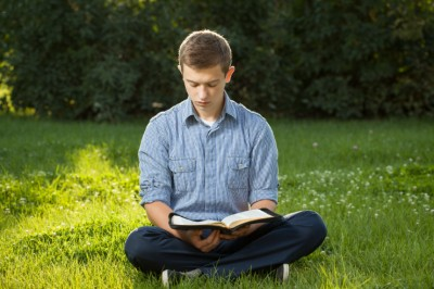 young-man-reading-bible-in-park-featured-w740x493